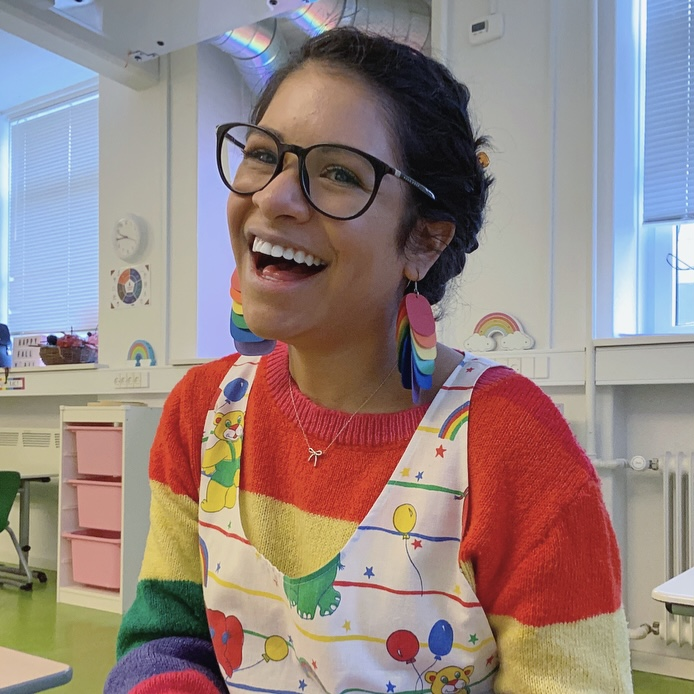 Angie is sitting in her classroom. She wears a rainbow sweater and a white dress with rainbows and animals. She has on glasses and rainbow earrings. She is smiling.